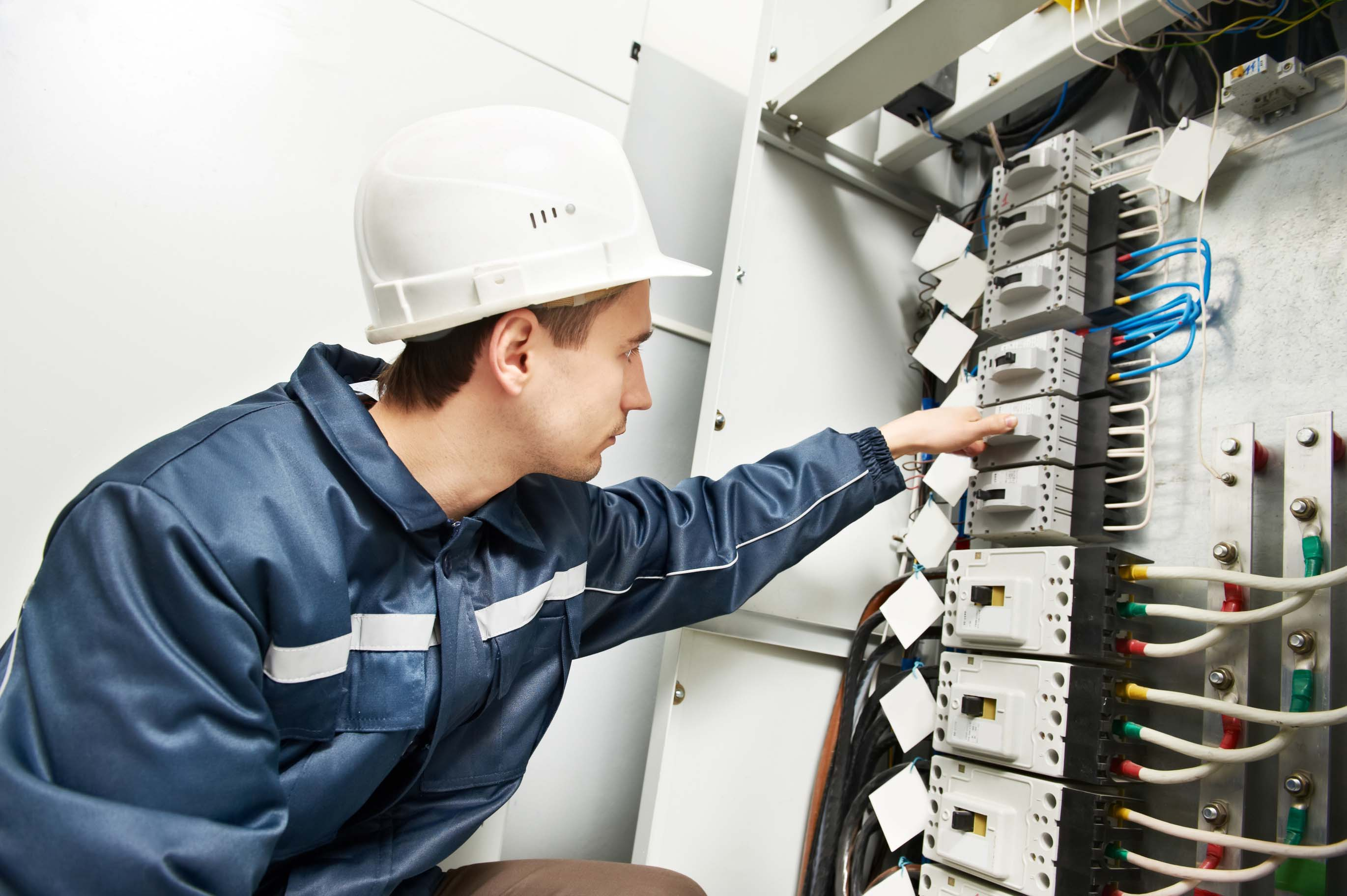 One electrician builder at work inspecting high voltage power electric line distribution fuseboard switching on